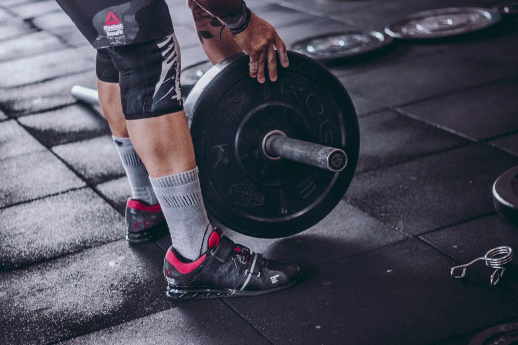 man putting weight plate on barbell